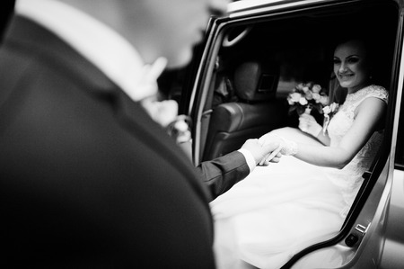 limousine: the groom takes the bride hand in the car Stock Photo