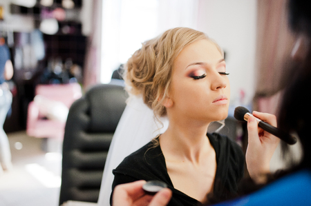 Young blonde bride applying wedding make-up by make-up artist