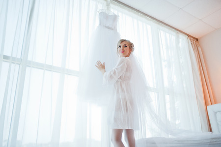 looked: gentle bride in gown looked at her wedding dress Stock Photo