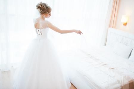 tenderly: gentle blonde  bride on couch tenderly posed