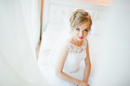 tenderly: gentle blonde  bride on couch tenderly posed