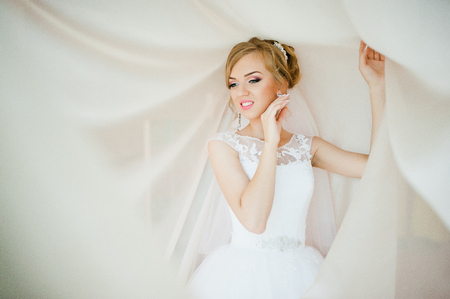 posed: gentle blonde  bride on curtains tender posed