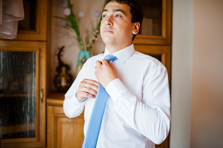businesswear: groom  gets dressed in formal wear and blue suit
