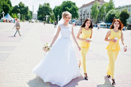 arrangment: bridesmaid at yellow dresses walking and bride Stock Photo