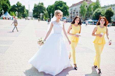 bridesmaid: bridesmaid at yellow dresses walking and bride Stock Photo