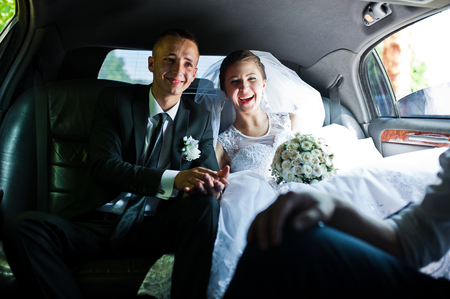 happy wedding couple sitting in limo