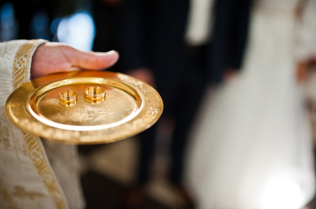 christian marriage: wedding rings on discus at hand of priest