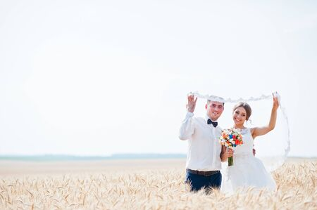 happy wedding: fashionable and happy wedding couple  at wheat field at sunny day Stock Photo