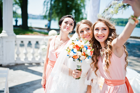 bridesmaid: bride with bridesmaid at wedding ceremony doing selfie Stock Photo