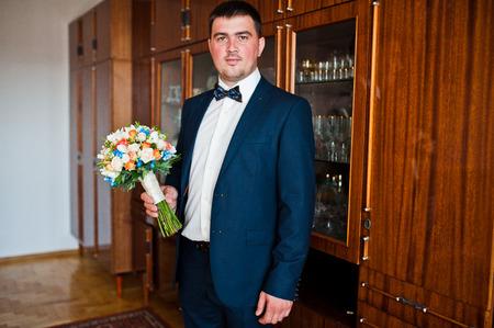 wrist cuffs: wedding bouquet at hand of groom Stock Photo