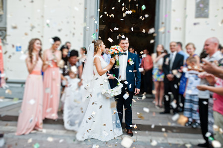 people in church: wedding couple come out from church under petals of roses. blur effect Stock Photo