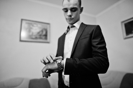 looked: Young groom man looked at his watch