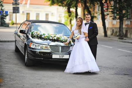 Wedding couple stay near black luxury limousine Zdjęcie Seryjne