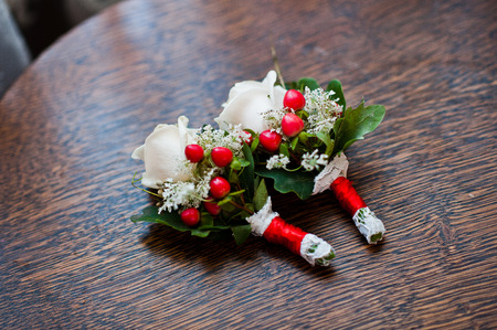 buttonhole: Buttonhole with red ribbons on wodden table