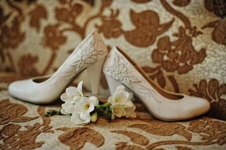 wedlock: Wedding shoes with buttonhole on texture background