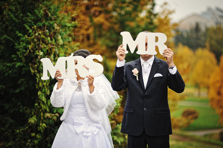 mr and mrs: Happy wedding couple in autumn day with sign mrs & mr