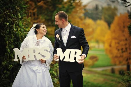 mr: Happy wedding couple in autumn day with sign mrs & mr