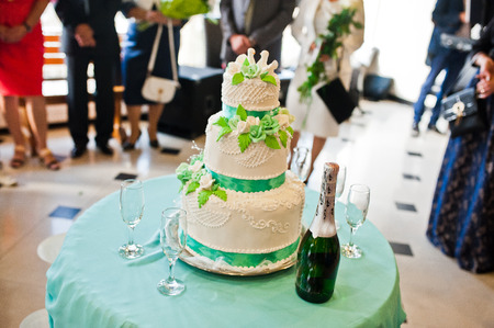 small table: Wedding cake with champagne and glasses at small table Stock Photo