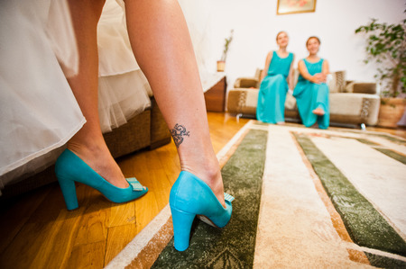 cinderella shoes: Turquoise shoes on tatoo legs of bride background bridesmaids Stock Photo