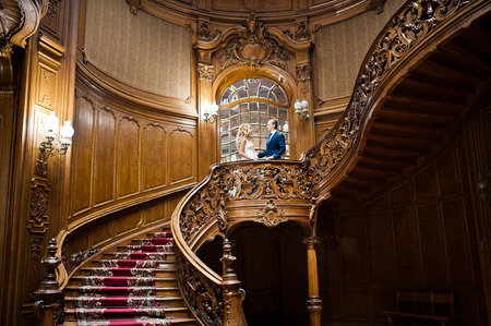 king palace: Elegant wedding couple at old vintage house and palace with big wooden stairs Stock Photo