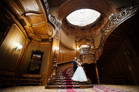 Elegant wedding couple at old vintage house and palace with big wooden stairs Foto de archivo