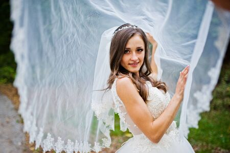 coquettish: Young coquettish brunette bride play with veil