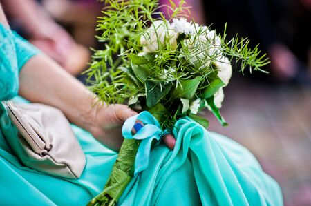 bridesmaid: Wedding bouquet on hand of bridesmaid on turquoise dress Stock Photo