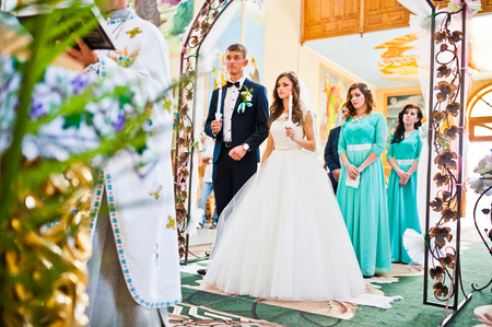 新婦付け添人の宿泊のアーチの下の教会の結婚式のカップル