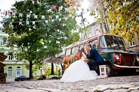 pompous: Wedding couple near old retro bus car