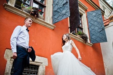 pompous: Wedding couple near orange house with windows Stock Photo