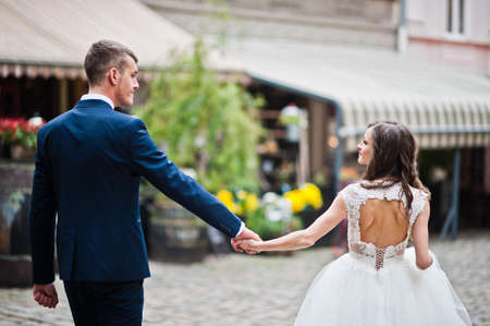 pompous: Wedding couple walking on streets old city Lviv