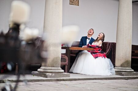 pompous: Newlyweds sitting at the table and laugh out loud , bride with blankets Stock Photo