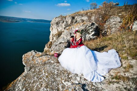 horizont: Charming bride in a wreath and elegant groom on landscapes of mountains, water and blue sky at sunny weather