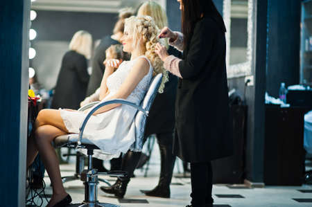 coiffeur: Hairdresser coiffeur makes hairstyle of gentle blonde bride