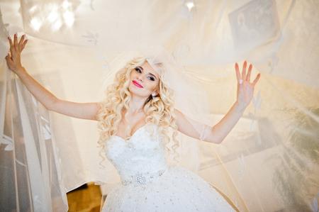 cabello rizado: Rizado rubio novia posando en cortinas
