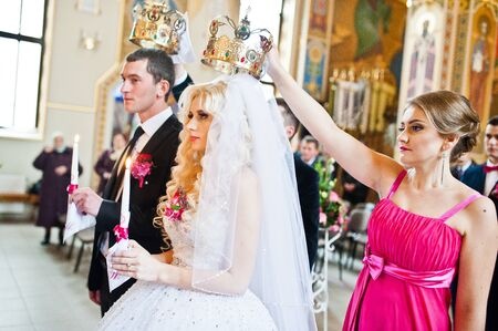 catholic wedding: Bridesmaid holding crown on had of newlyweds at churh
