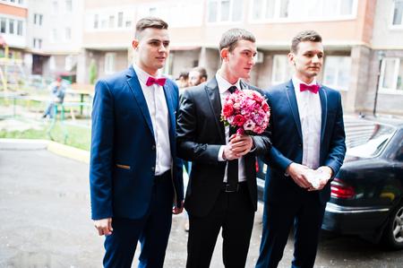 wedding customs: Groom with groomsman background wedding cars Stock Photo