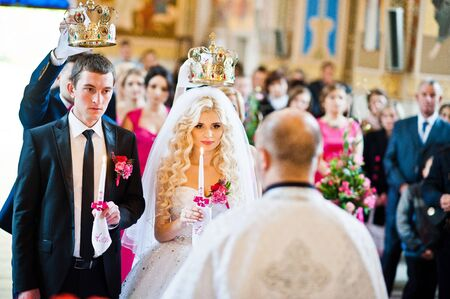 debutante: Wedding couple at church with candles at hands and crowns at hads
