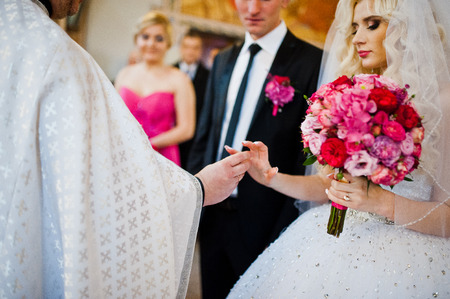 debutante: Priest wears a wedding ring on the hand of the bride
