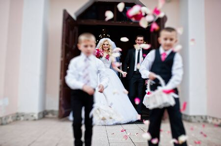 debutante: Wedding couple out from church registration, children strew petals of roses