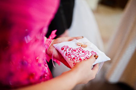 shiny suit: Bridesmaid holding little pillow with wedding rings