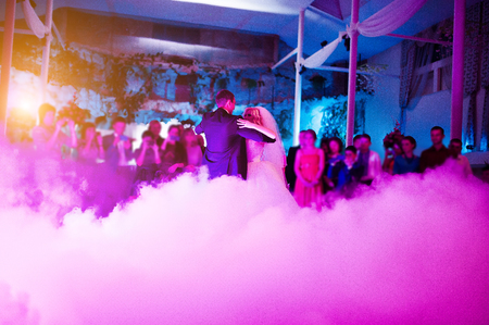 낮은 핑크 빛과 무거운 연기에 신혼 부부의 놀라운 첫 번째 결혼식 댄스