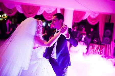 Erstaunlich erste Hochzeitstanz der Jungvermählten auf niedrigem rosa Licht und starker Rauch