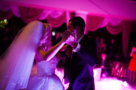 butonniere: Amazing first wedding dance of newlyweds on low pink light and heavy smoke