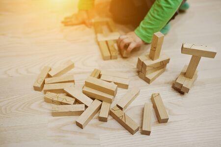 developmental: Hand of baby who played developmental game of wooden blocks lumber Stock Photo