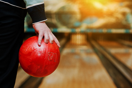 strike: Bowling ball at hand of man background bowling alley Stock Photo