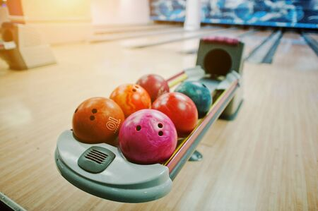 on strike: A group of colored bowling balls at bowl lift
