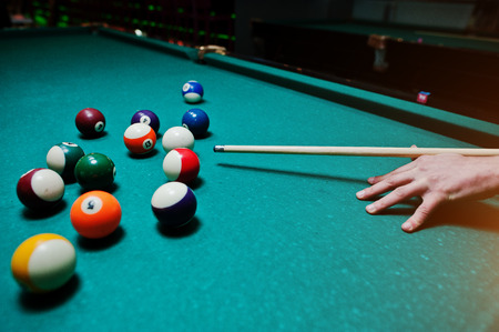 bola de billar: hombre de mano que sostiene taco de billar para disparar bolas