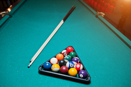pool cue: Billiard balls in a pool table at triangle with billiard cue