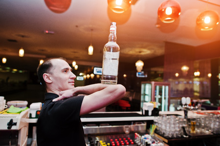 bartending: Barman hold bottle on elbows of hand at the bar Stock Photo